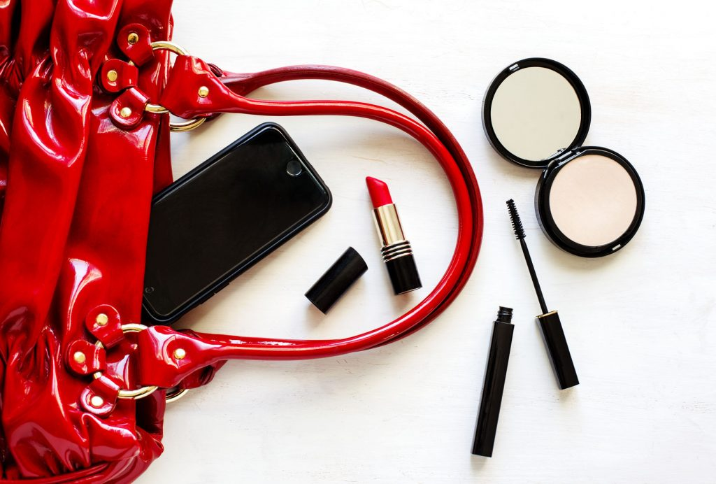 52244481 - women's set of fashion accessories on wooden background: shoes, handbag, cell phone and cosmetics