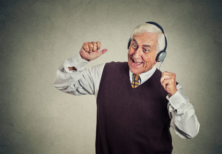 38602458 - closeup portrait elderly man, senior retired guy with headphones listening to the radio, enjoying music and his life isolated on gray wall background. positive human emotions, face expression
